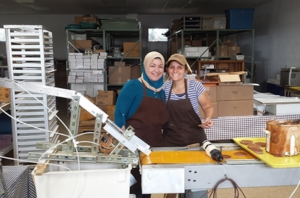 Suha, left, a refugee from Iraq, helps to make Stroopies with The Stroopie Co. co-owner Jennie Groff.